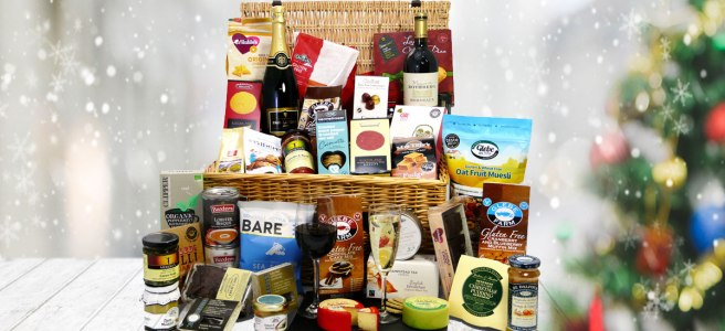 Wicker hamper filled with gluten free food and drink next to Christmas tree